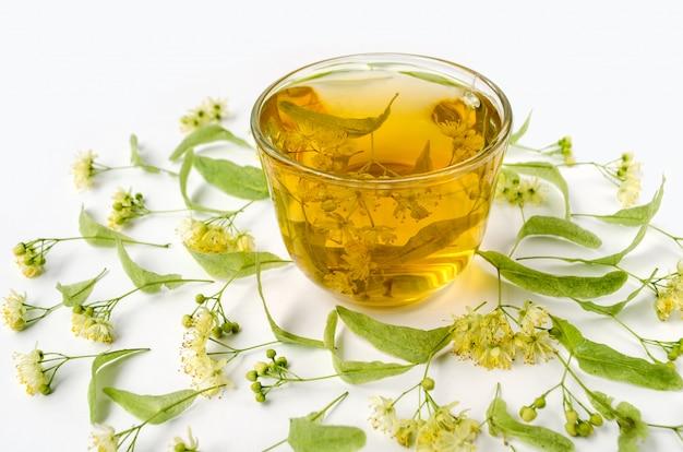 Herbata z lipy w przezroczystym kubku z kwiatami limonki.