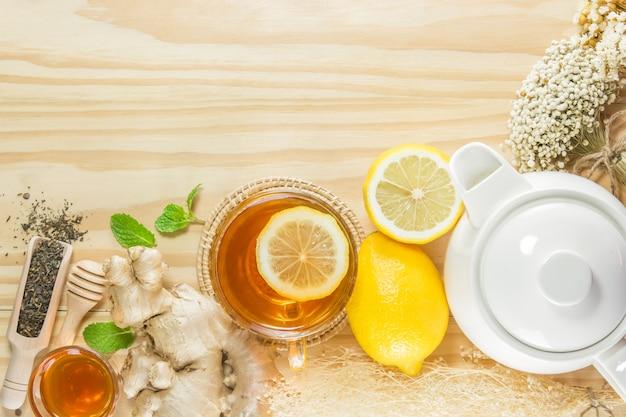 Herbata z miętowym miodowym imbirem i cytryną na drewnianym tle.