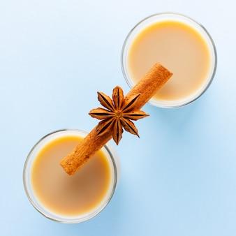 Herbata z mlekiem i przyprawami na niebieskim tle. masala chai w filiżankach tureckiej herbaty. indyjski napój narodowy na pastelowym tle.