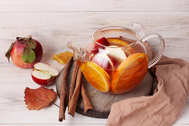 Herbata z owocami i jagodami w szklanym czajniczku na białym drewnianym tle