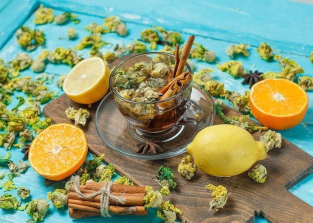 Herbata z przyprawami, pomarańcza, cytryna, suszone zioła w kubku na niebiesko i deska do krojenia, duży kąt widzenia.