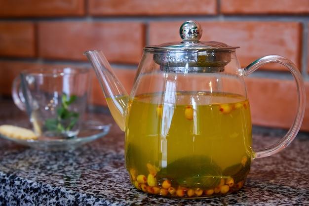 Herbata z rokitnika i mięty w przezroczystym szklanym imbryku
