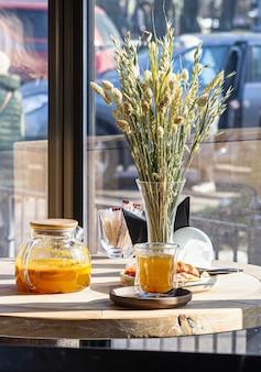 Herbata z rokitnika w imbryku i szklanym kubku i wazonie z pszenicznymi uszami na drewnianym stole w kawiarni