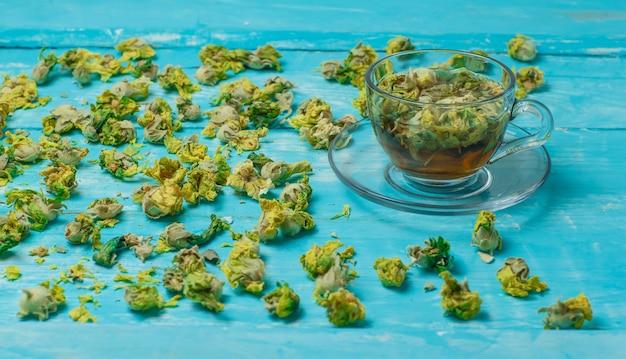 Herbata z suszonymi ziołami w szklanym kubku na niebieskim drewnie, wysoki kąt widzenia.