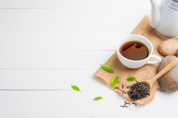 Herbata z szklanką herbaty na białym drewnie