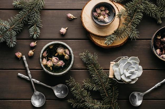 Herbata z widokiem z góry z suszonymi kwiatami i gałązkami sosny