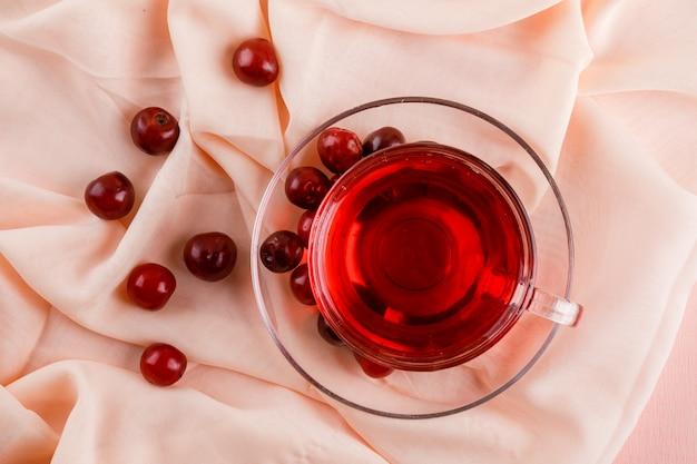 Herbata z wiśniami w szklanym kubku na różu i tkaninie.