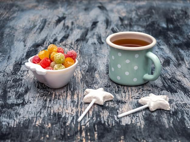 Herbata ze słodyczami w świąteczny poranek. marmolady i lizaki czekoladowe.