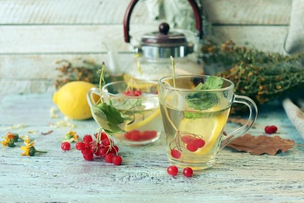 Herbata ze zdrowymi ziołami, kwiaty jagody i cytryny w szklanej filiżance na drewnianym tle