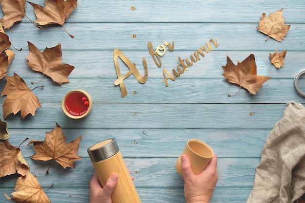 Herbata zero waste jesienią. ręce trzymające izolowaną metalową kolbę i bambusowy kubek, porozrzucane jesienne liście jaworu.