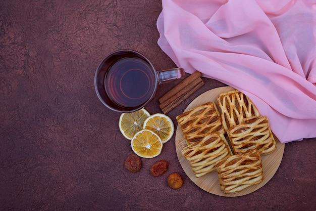 Herbata ziołowa i ciasteczka z dżemem na drewnianym stole. pojęcie śniadanie, domowe ciasta, słodycz.