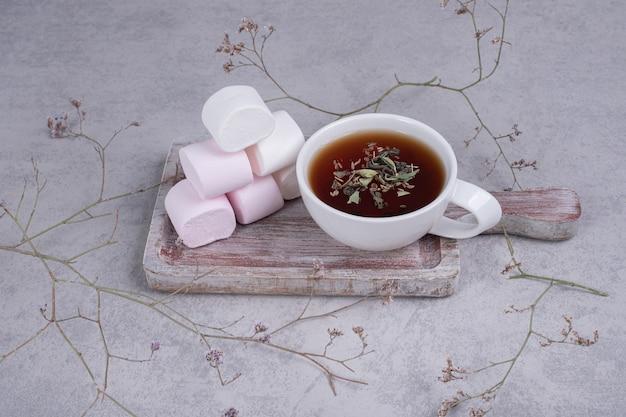 Herbata ziołowa i talerz pianek na szarym tle. wysokiej jakości zdjęcie