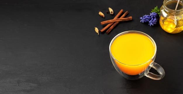 Herbata ziołowa kurkuma i przyprawy na czarnej powierzchni