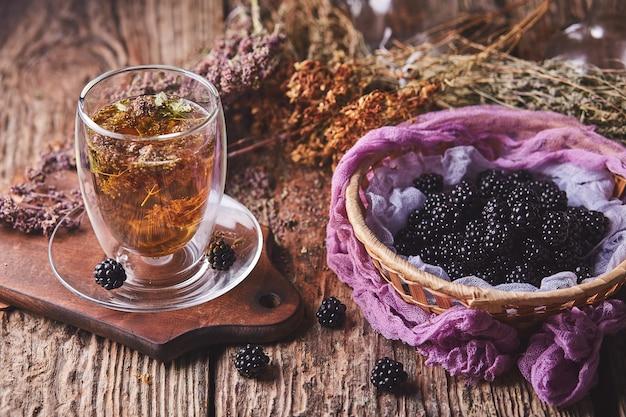 Herbata ziołowa, kwiatowa i jeżyny na drewnie
