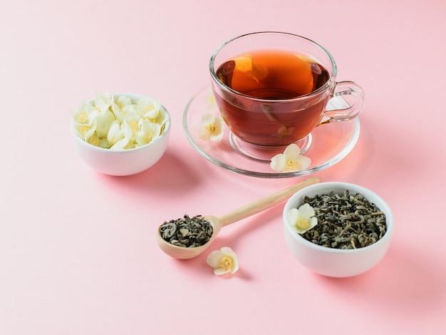 Herbata ziołowa, miód, kwiaty jaśminu i drewniana łyżka na różowym stole. skład porannego śniadania. kolor pastelowy.