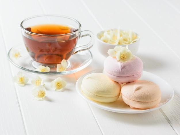 Herbata ziołowa, miska pianek i kwiatów jaśminu na białym stole. skład porannego śniadania.