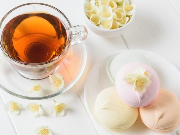 Herbata ziołowa, miska pianek i miska kwiatów jaśminu na białym stole