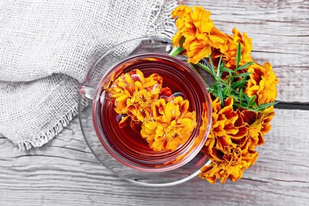 Herbata ziołowa nagietka w szklanej filiżance i spodku, świeże kwiaty, konopie na tle deska z góry