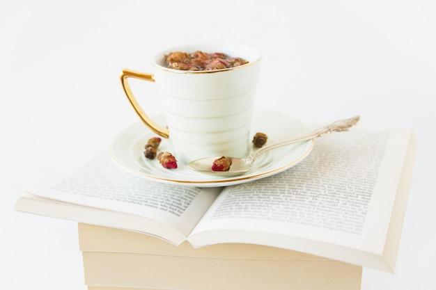Herbata ziołowa suszonych róż w filiżance i łyżce. gorący zdrowy napój na otwartej księdze. biała powierzchnia. minimalistyczny styl. miejsce. widok z góry.