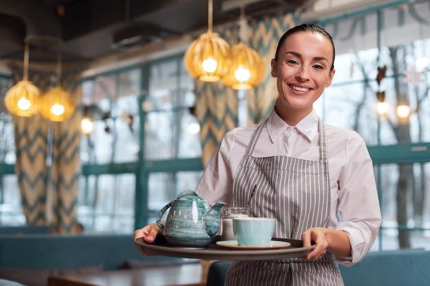 Herbata ziołowa. szczęśliwy całkiem uroczy kelnerka trzymając tacę, patrząc na kamery i pozowanie na niewyraźne tło