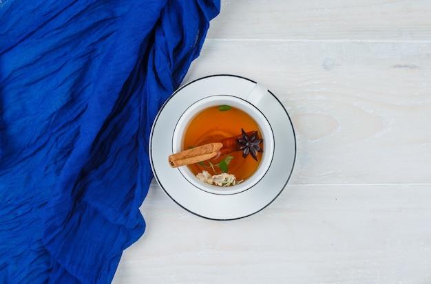 Herbata ziołowa w białej filiżance i niebieskim szaliku