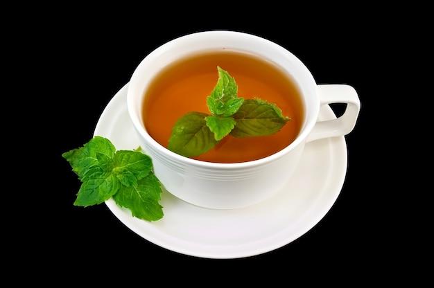 Herbata ziołowa w białej porcelanowej filiżance z dwoma gałązkami mięty na białym tle