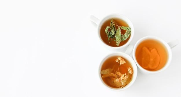 Herbata ziołowa w białych filiżankach z suszonymi liśćmi mięty, kwiatami lipy i cytryną na białym talerzu