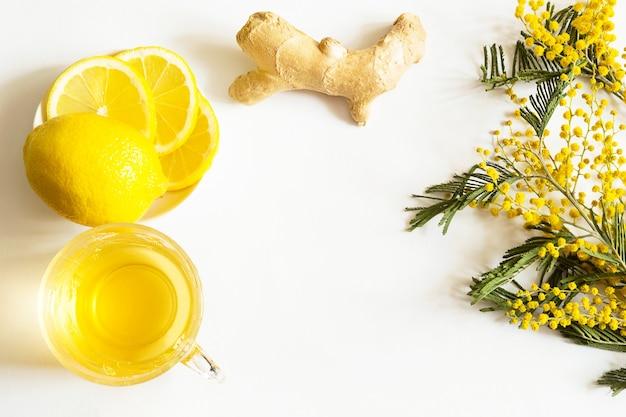 Herbata ziołowa w filiżance, imbir, cytryna i akacja. widok z góry, płaski układ