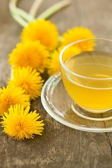 Herbata ziołowa w szklanej filiżance i kwiaty na drewnianym stole