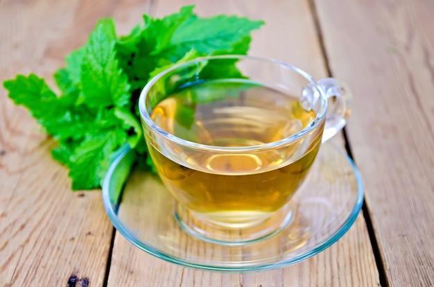 Herbata ziołowa w szklanym kubku, świeże liście melisy na tle drewnianych desek