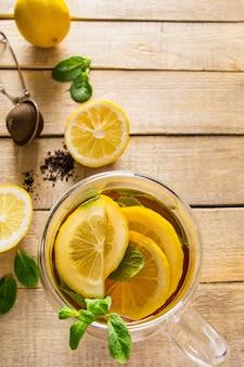 Herbata ziołowa z cytryną i miętą na drewnianym