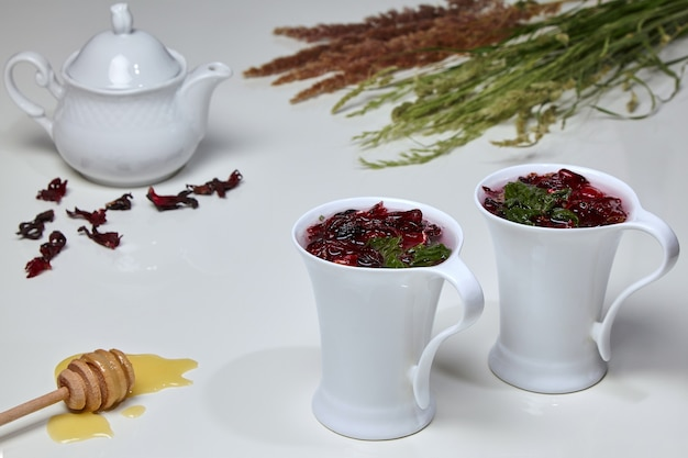 Herbata ziołowa z hibiskusa z sudańskich kwiatów róży i mięty w eleganckich białych filiżankach na białym stole otoczona miodem, czajniczkiem i bukietem dzikich ziół