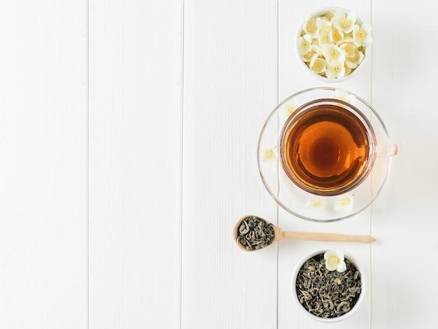 Herbata ziołowa z jasmine i miską kwiatów na białym stole