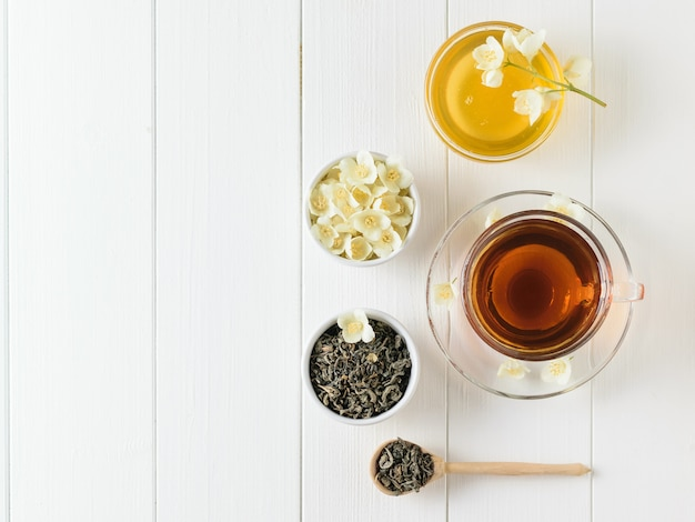 Herbata ziołowa z jaśminem i miska kwiatów i miodu na białym stole. skład porannego śniadania. leżał płasko.