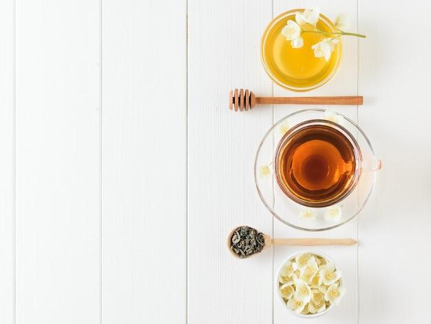 Herbata ziołowa z jaśminem i miska kwiatów i miodu na rustykalnym stole