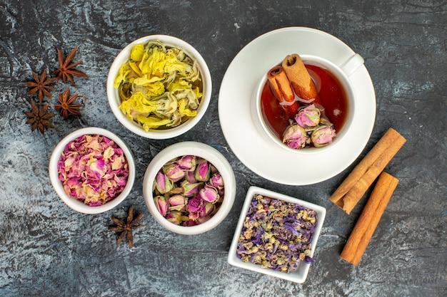 Herbata ziołowa z laskami cynamonu i suszonymi kwiatami oraz anyżem na szaro