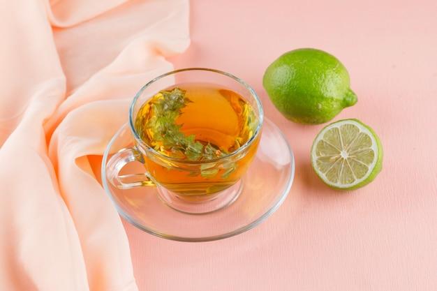 Herbata ziołowa z limonkami w szklanej filiżance na różowym i tekstylnym, wysokim kącie widoku.