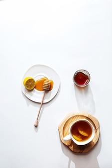 Herbata ziołowa z miodem i cytryną na jasnym tle