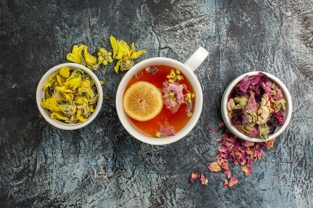 Herbata ziołowa z miseczkami suszonych kwiatów na szaro