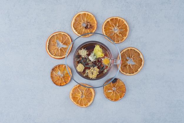 Herbata ziołowa z suszoną pomarańczą na szarej powierzchni