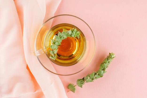 Herbata ziołowa z ziołami w szklanej filiżance na różowo i tekstylnie, leżała płasko.