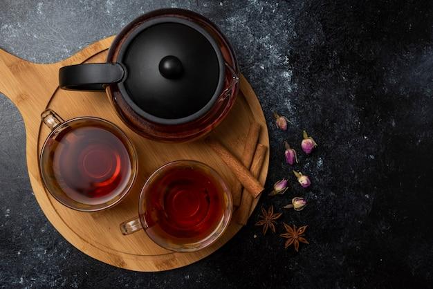 Herbata ziołowa zimowa w filiżankach z przyprawami na desce.