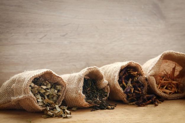 Herbata ziołowa znajduje się w brązowej torbie worek umieszczonej na drewnianej podłodze.