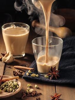 Herbatę masala z przyprawami nalewa się do szklanych kubków na drewnianym stole.