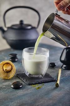 Herbatę matcha wlewa się do szklanki ze srebrnego dzbanka
