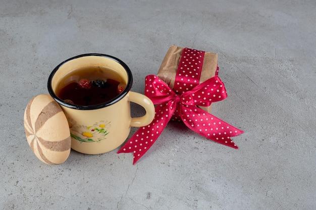 Herbatka owocowa, ciastko i opakowanie prezentowe na marmurowej powierzchni.