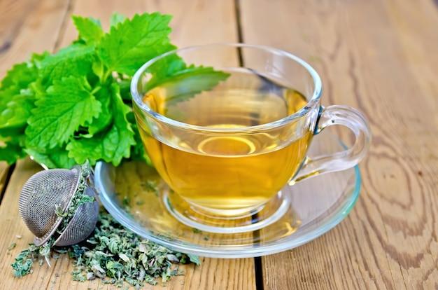 Herbatka ziołowa w szklanej filiżance, metalowe sito z suchymi listkami mięty, świeże listki mięty na deskach