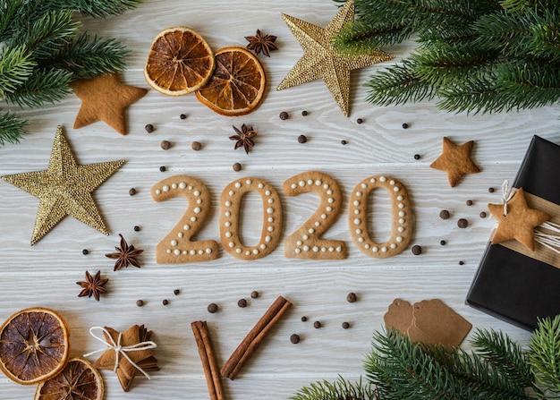 Herbatniki imbirowe w postaci liczb i noworoczne imbirowe ciasteczka 2020 białe drewno. widok z góry. opakowania sezonowe, przyprawy i atrybuty noworoczne