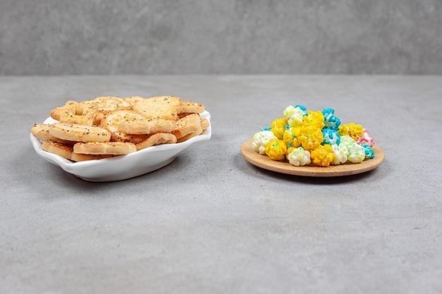 Herbatniki na ozdobnym talerzu obok małej drewnianej tacy z popcornowymi cukierkami na marmurowej powierzchni.