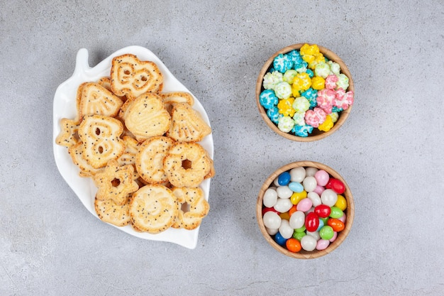 Herbatniki na ozdobnym talerzu obok misek cukierków na marmurowej powierzchni.